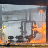Fire fighters battling remains of a fire explosion at an oil refinery