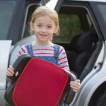 Portrait Of Girl Holding Booster Seat Standing Next To Car