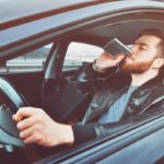 A drunken man driving a car with a bottle of alcohol in his hand. Man whiskey from an iron flask behind the wheel of a car