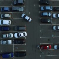Drone footage cars parking at congested parking lots. people walking parking