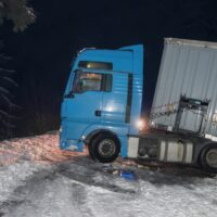 A real accident. Truck traffic accident at night, on a snowy winter road. Broken truck on the road in the snow.