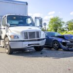 Road accident with damage to vehicles as a result of a collision between a semi truck with box trailer and a car